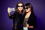 Attractive it girls in trendy sunglasses taking selfie on smartphone before starting to celebrate New Year, waist-up portrait