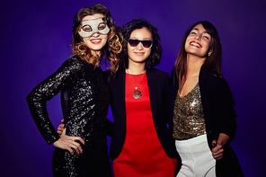 Three glamorous party goers standing against dark background and looking at camera with charming smiles, group portrait