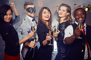 Waist-up group portrait of elegant-looking young people looking at camera with wide smiles while celebrating momentous event in night club