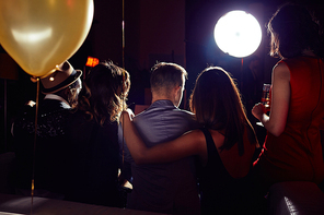 Back view of two young couples hanging out with friends at home party, they sitting on sofa and drinking champagne