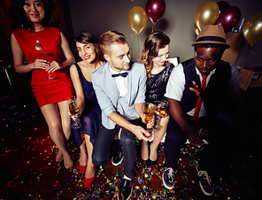 High angle view of multi-ethic group of friends partying at trendy night club and celebrating New Years Eve, full-length portrait