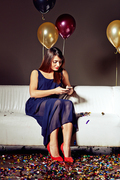 Full length portrait of attractive young woman texting with her friend on smartphone while sitting on sofa at night club
