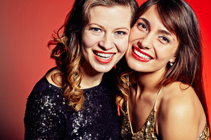 Head and shoulders portrait of pretty young women standing cheek to cheek against red background and looking at camera with toothy smiles