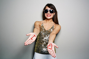 Waist-up portrait of pretty young woman in sunglasses stretching hands to camera while standing against white background, inscription I and heart symbol written on palms with red gouache