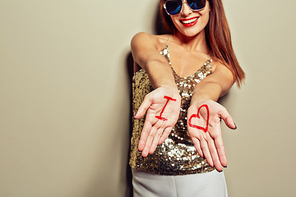 Pretty young woman wearing sunglasses posing for photography and stretching palms with inscription I and heart symbol to camera, studio shot