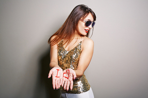 Studio shot of attractive young woman looking away while standing against white background and showing palms with inscription I and heart symbol to camera