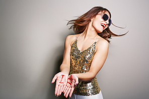 Stylish portrait of attractive young woman in sunglasses turning head away from camera and stretching palms with inscription I and heart symbol, studio shot