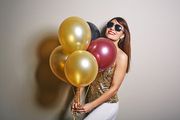 Waist-up portrait of beautiful young woman holding bunch of colorful balloons in hands and looking at camera with toothy smile, studio shot