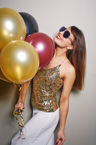 Profile view of cheerful young woman standing against white background and holding bunch of colorful balloons in hand, studio shot