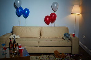 Empty room with couch, lamp, balloons, disco-ball, teddybears and drinks after party