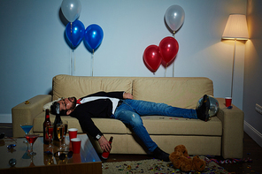 Completion of wild party: middle-aged man with beer bottle in hand sleeping on sofa, plastic cups, empty alcohol bottles and colorful confetti observed everywhere