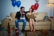 Middle-aged Asian man flirting with pretty young woman and pouring champagne into her flute, she enjoying night while sitting on couch in living room