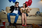 Full-length portrait of multiethnic couple celebrating New Year together: they sitting on couch and enjoying each others company
