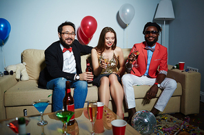 Two bearded men with beer bottle and champagne flute looking at camera while their pretty female friend sitting between them