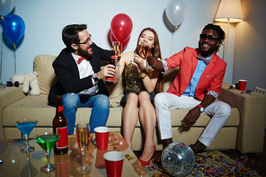Pretty young lady in stylish clothes sitting with her male friends in living room and clinking glasses together