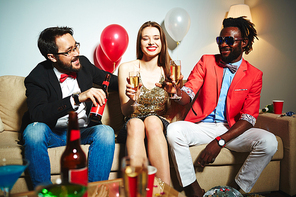 Attractive young woman with wide smile chatting and drinking alcohol with her male colleagues while having company party