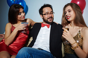 Bearded Asian businessman with bow tie slightly embracing two pretty women while sitting between them, they having good time in nightclub