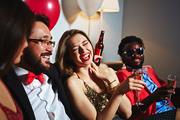 Portrait of cheerful young woman with red lipstick holding champagne flute in hand and laughing at funny story told by her Asian friend