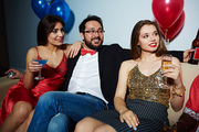 Male and female clubbers celebrating momentous event with alcohol: they sitting on couch and looking away joyfully