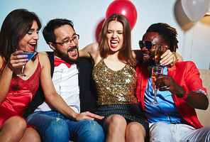 Joyful young woman in shiny top slightly embracing her Asian and Afro-American friends while posing for photography during lovely house party