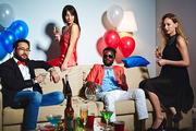 Stylish Afro-American man in sunglasses sitting in living room and holding disco ball in hand, two pretty woman and Asian man with champagne flutes and cocktail glass enjoying night