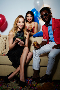 Portrait of young blond-haired woman with cocktail glass looking at camera with wide smile while Afro-American man sitting next to her and pretty black-haired woman standing behind couch