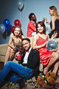 Well-dressed colleagues with champagne flutes and beer bottle posing for photography while Afro-American man and blond-haired woman standing behind them and clinking glasses together