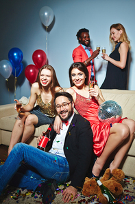 Attractive young women with champagne flutes and Asian man with beer bottle posing for photography on foreground while multiethnic couple toasting on background