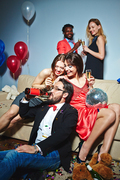 Joyful girls with champagne laughing at guy drinking beer from bottle at party