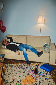 Messy room after wild party: colorful confetti thrown everywhere, empty alcohol bottles and champagne flutes standing on floor and coffee table, Asian man sleeping on couch