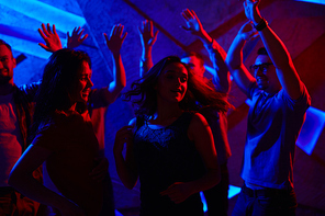 Two girls enjoying dance at disco with guys on background