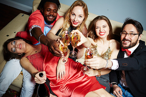 Two middle-aged men and two young women looking at camera while toasting with champagne flutes, tipsy lady with closed eyes lying on their laps and holding alcohol bottle in hand