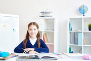 Pretty schoolgirl sitting by desk at lesson of reading
