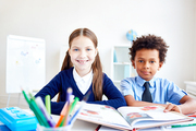 Intercultural pupils of junior school at lesson of reading