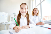 Smiling schoolgirl drawing or making notes in her copybook with classmate near by
