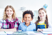 Cheerful kids sitting by desk in classroom with open book in front of them