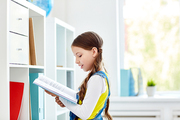 Diligent schoolgirl with open book reading by shelf in school library