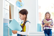 Schoolgirl choosing book in library for lesson of literature