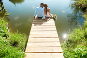 Backs of bride and groom sitting on pontoon by lake