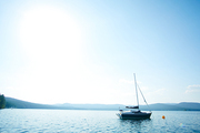 Empty yacht in water among mountains on sunny day