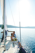 Amorous bride and groom traveling by yacht on sunny day