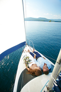 Relaxed man and woman floating by yacht