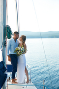 Affectionate married couple standing on yacht