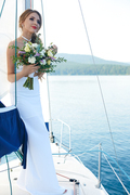 Attractive bride in white wedding dress floating by yacht
