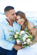Young woman with flowers looking at camera with smile while her husband embracing her
