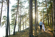 Backs of newlyweds walking down forest path