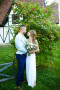 Young bride and groom standing by green tree in natural environment