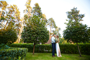 Bride and groom standing on green grass in garden