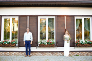 Smiling bride and groom standing by rural edifice with small flower-beds on windows