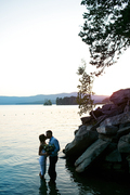 Couple of amorous newlyweds kissing at sunset